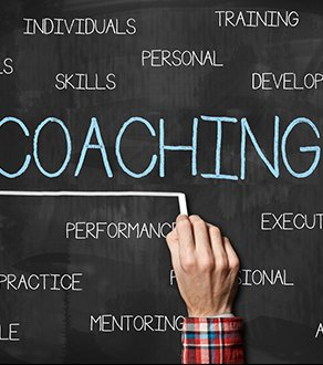 Man writing COACHING on a blackboard