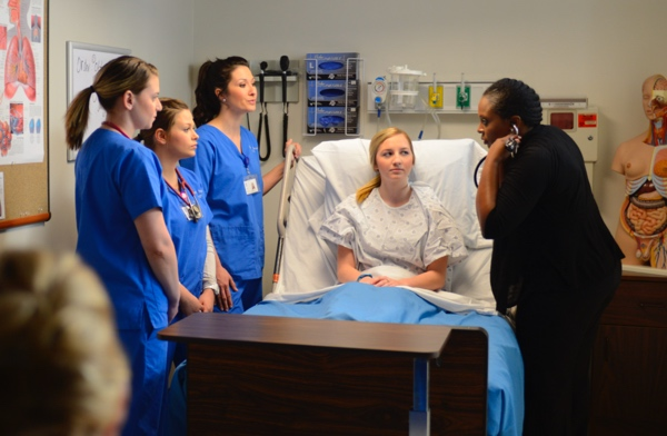 Group of nursing students gathered around a bed