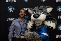 Man standing and smiling with Bryant & Stratton College mascot Blue the Bobcat