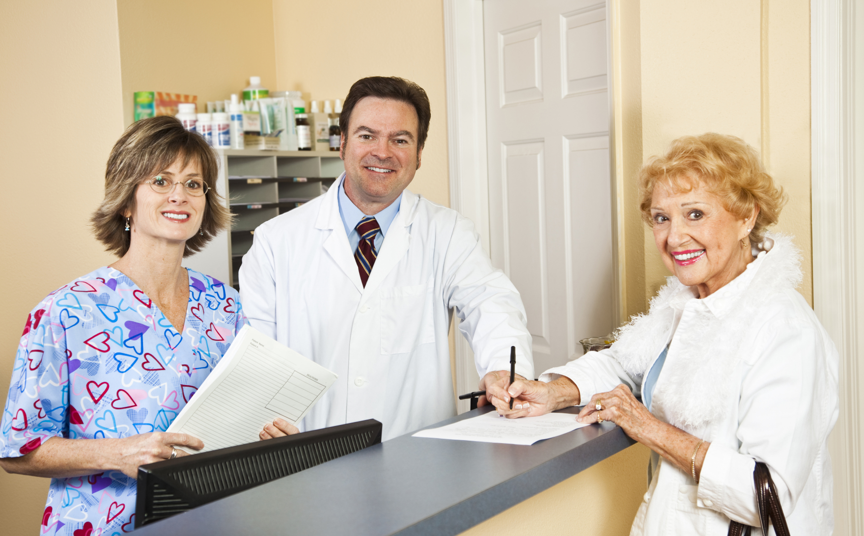 Doctor and Nurse with patient at desk