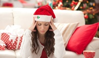 Stressed out woman wearing a Santa cap and rubbing her head.