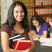 Smiling student holding books in a library