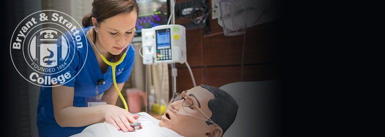 Nursing student working with medical dummy