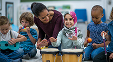 Teacher playing drums with student