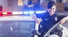 Woman Officer leaning against police car