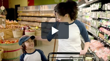 Video Play button over image of mother shopping with son.